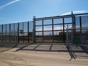 Landing mat, high mesh and chain link-gate leads to interior border road